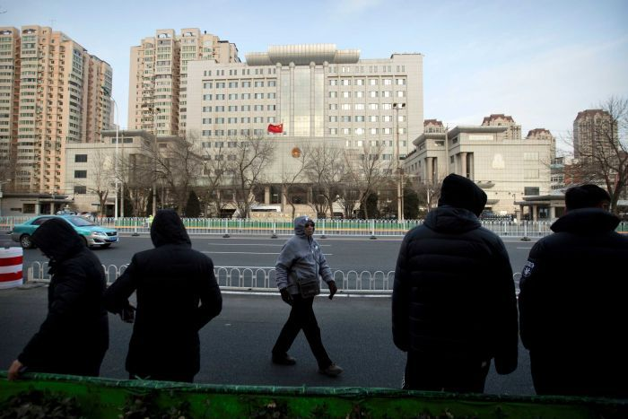 Plainclothes security officers stand in the street opposite  Tianjin No.2 Intermediate court.