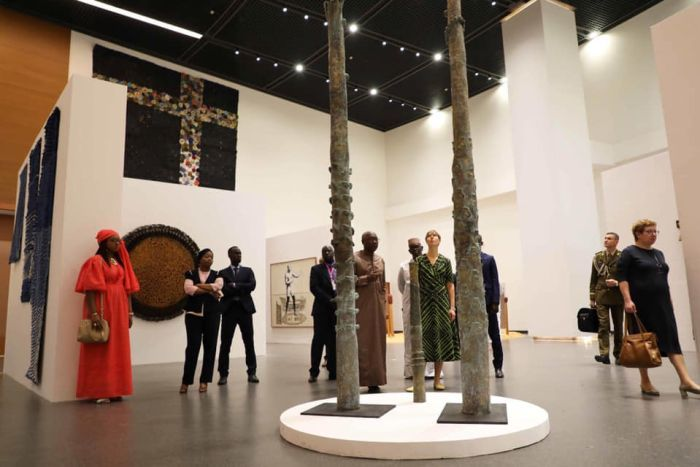 Visitors view various artworks in the shape of poles at varying heights at the Museum of Black Civilisation.