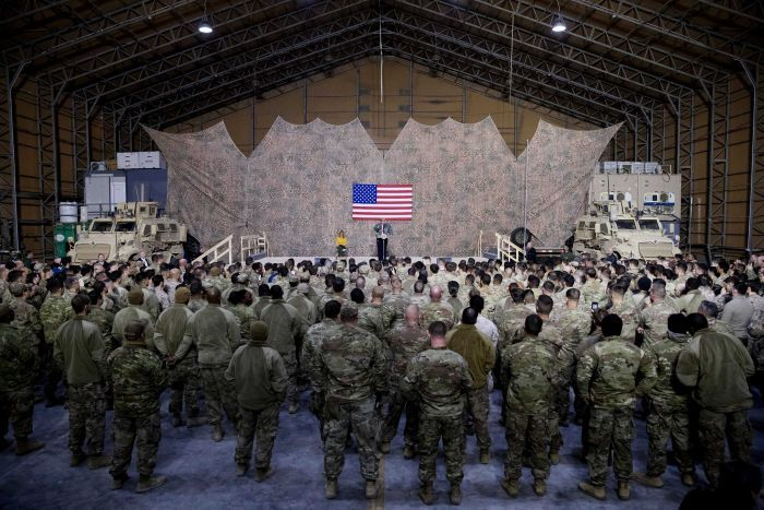 A wide-shot of an air hangar shows a crowd of US troops in camo listening to President Donald Trump.