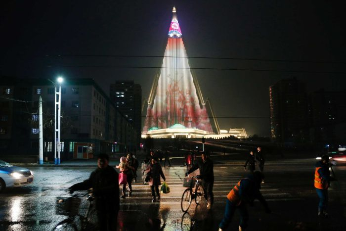People cross a street as pyramid-shaped Ryugyong Hotel is seen in the background.