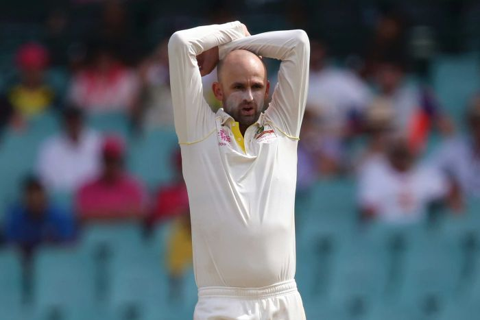 Australia bowler Nathan Lyon, wearing sunscreen on his nose and cheeks, stands with his arms over his head during a Test match.