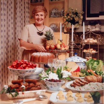 Woman stands before a table laden with food
