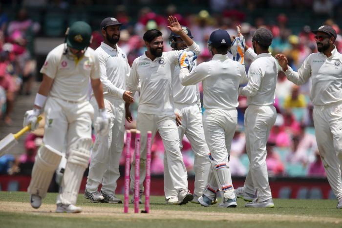 Australia batsman Marcus Harris walks past his broken stumps during the SCG Test as India players celebrate in the background.