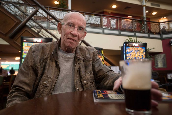 Bald man with glasses in a leather jacket sits at a high table with a pint of Guinness in front of him.