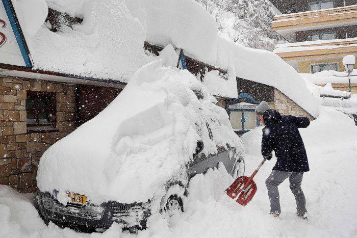 A man shovels snow from his car, parked next to a building and streets heaped with snow as it continues to fall.