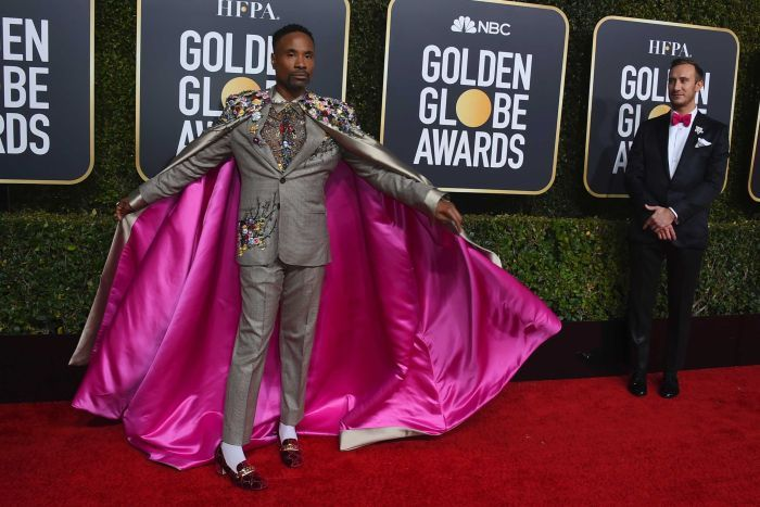 Billy Porter poses with a grey cape lined with pink silk on the red carpet.