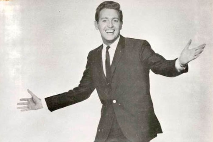A black and white publicity shot of Jimmy Hanna dressed in a suit and tie