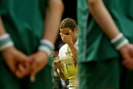 Roger Federer holds the Wimbledon trophy while hiding his face with the other hand, as ballboys stand watch in the foreground