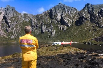 A firefighter stands next to a chopper at Lake Rhona