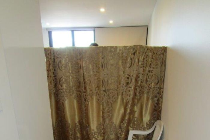 A gold curtain hides part of a room, with two white plastic chairs sitting outside.