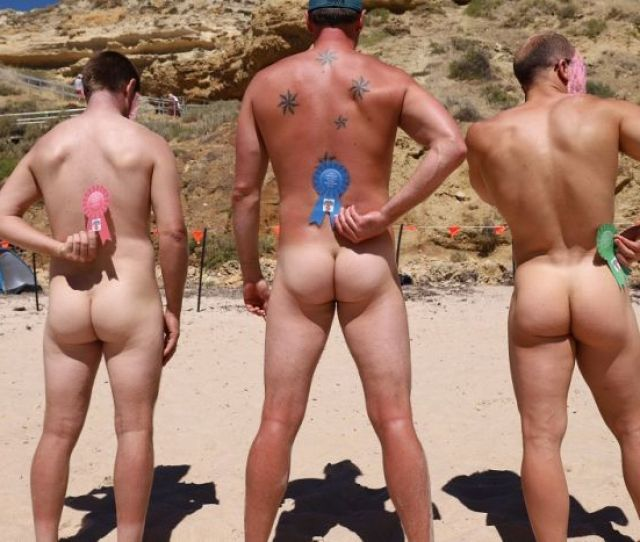 Three Nude Men Stand With Their Backs To The Camera Holding Winning Ribbons