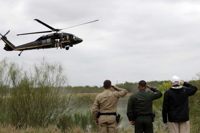 Three men, including Donald Trump, salute a customs helicopter flying low.
