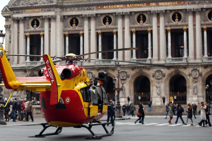 A yellow and red helicopter is parked in the middle of Paris's Place de l'Opera in front of the Palais Garnier