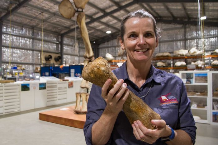 Robyn McKenzie general manager of the Eromanga Natural History Museum holding a fossil