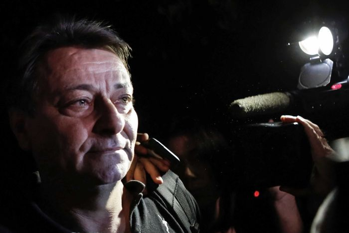 Cesare Battisti walks towards a throng of cameras with teary eyes as a person has a hand on his shoulder.
