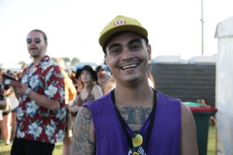 Man wearing a purple vest and yellow cap smiling at the camera