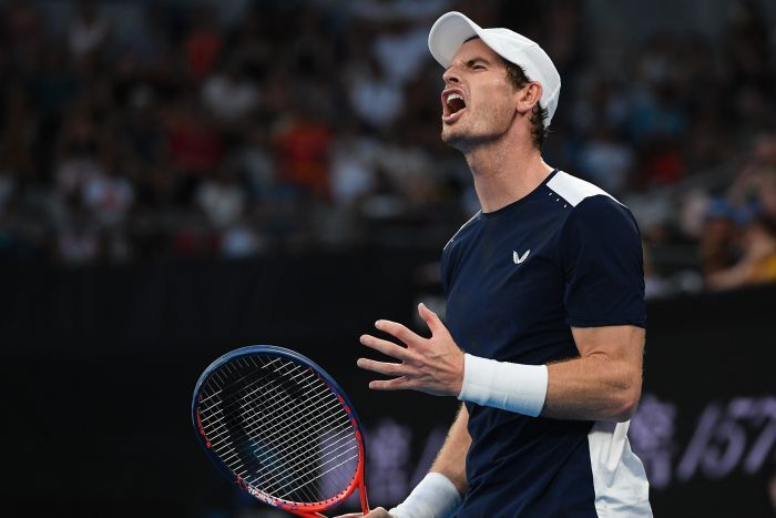 Andy Murray grimaces on court, clenching his hand in frustration after losing a point