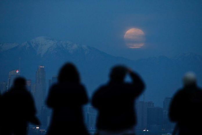 The reddish moon is visible behind some clouds above the mountain range.
