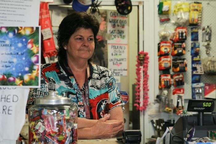 A woman stands behind a counter in a general store.
