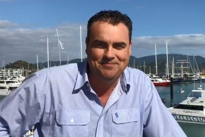 Whitsunday MP Jason Costigan smiling while standing at the marina in Airlie Beach.