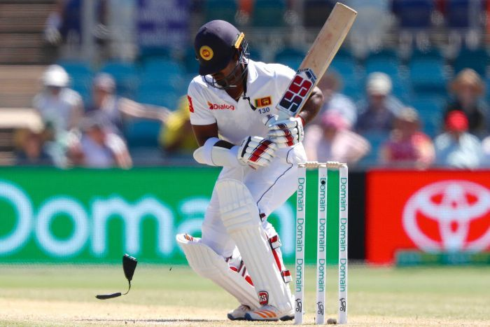 Kusal Perera crouches after he is hit on the helmet by a bouncer as his neck guard bounces to the turf