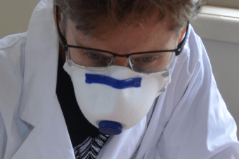 Adjunct researcher Dr Jackie Wright wears a lab coat and face mask as she swabs a meth test.
