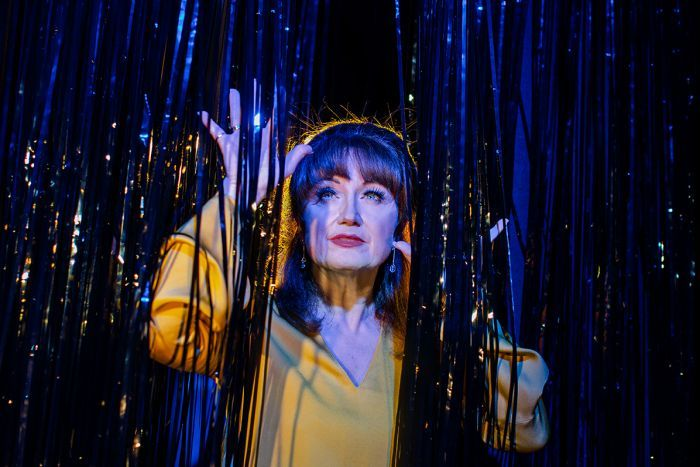 Colour photo of musical theatre actor Caroline O'Connor looking up and through tinsel curtain.