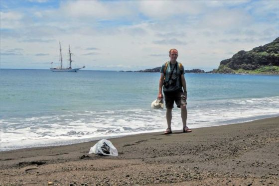 A man in shorts and t-shirt wearing a backpack and camera equipment stands on a black sand beach with a boat in the background