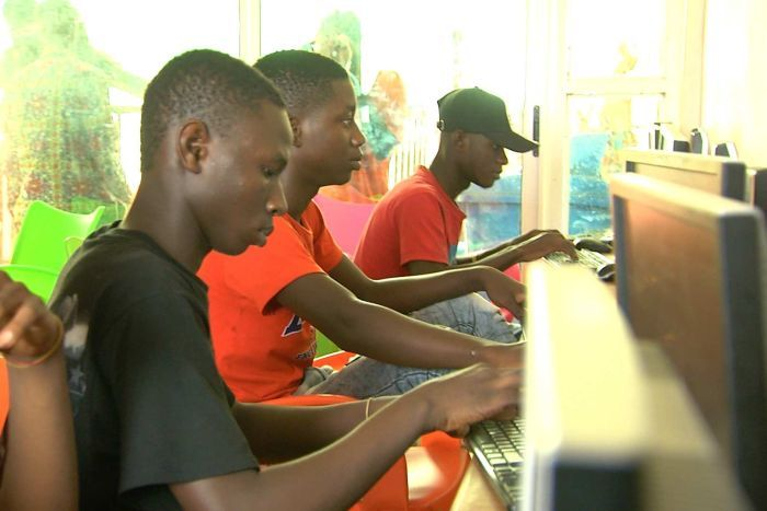 Four young men sit at computers in an internet cafe in Ghana.