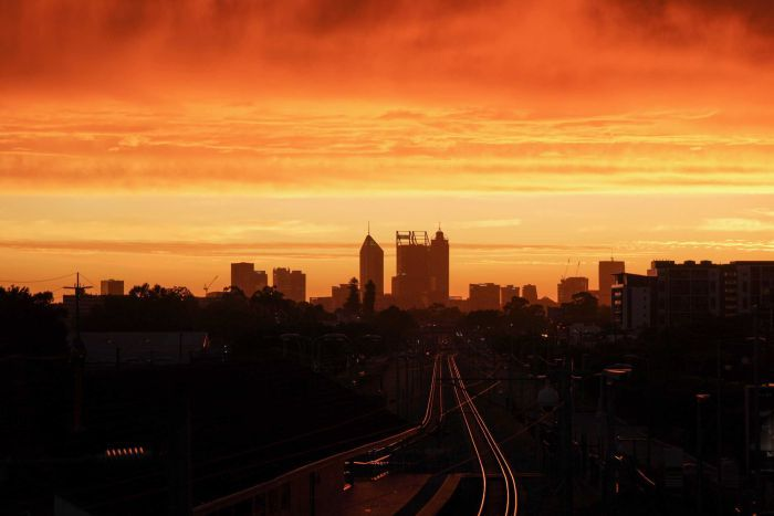 A long shot of Perth's CBD at sunset, with a bright orange and yellow sky enveloping the city skyline.