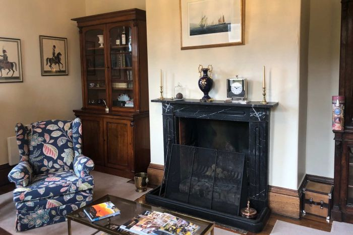 A loungeroom inside Prospect House with original features including a marbled fireplace
