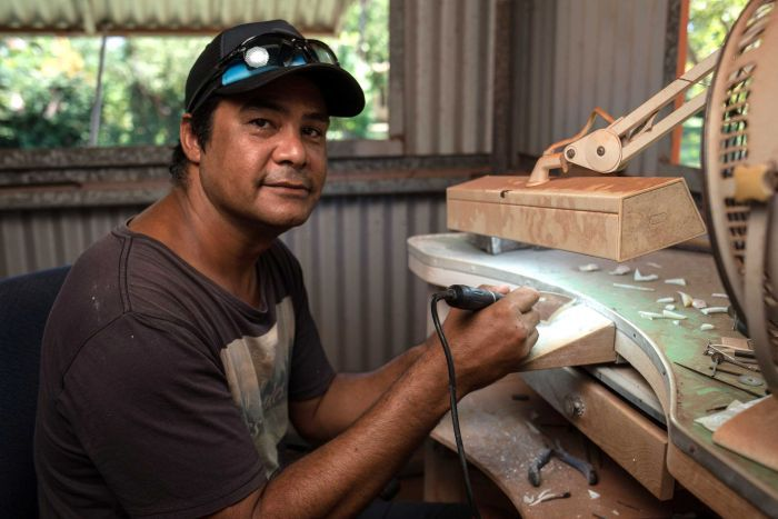 A mid shot of West Kimberley artist Garry Sibosado at an art bench posing for a photo carving a design into a pearl shell.