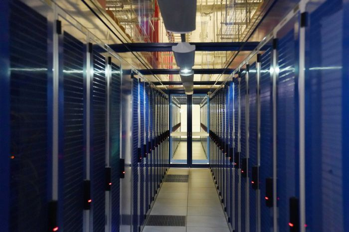 Two rows of servers in a dark room.