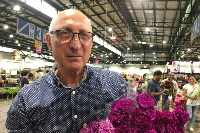 Bernard Pollack, a florist holding flowers in the Sydney flower market.