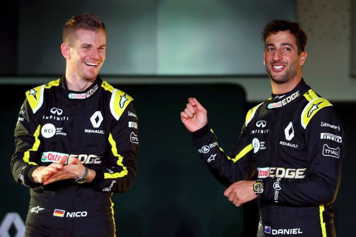 Two F1 drivers smile for the cameras at a season launch.