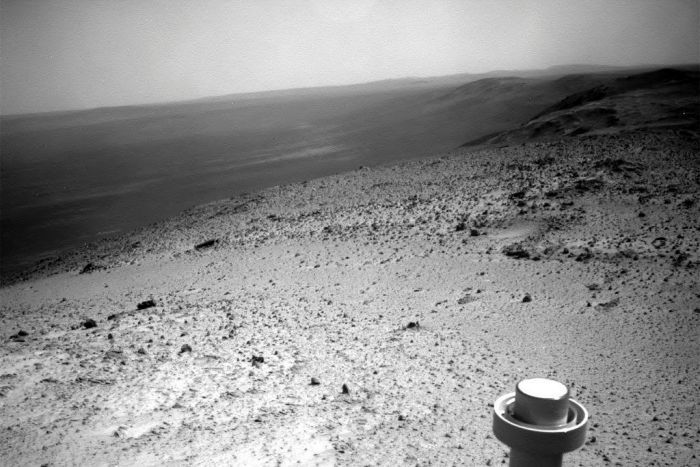 A black and white image shows a valley stretching from a hill on which a solar powered NASA rover is sitting.
