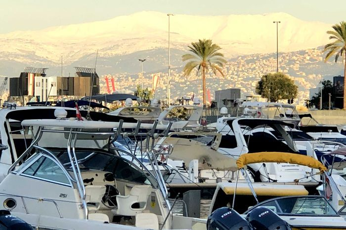 Snow on the mountains near Beirut, behind boats and palm trees