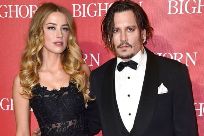 Amber Heard and Johnny Depp face a logo wall on a red carpet event, both in formal wear.