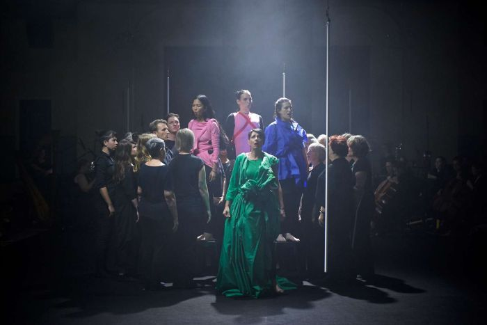 Cluster of performers centre stage, darkened backdrop, haze above the group, four soloists in colourful clothes sing at centre.