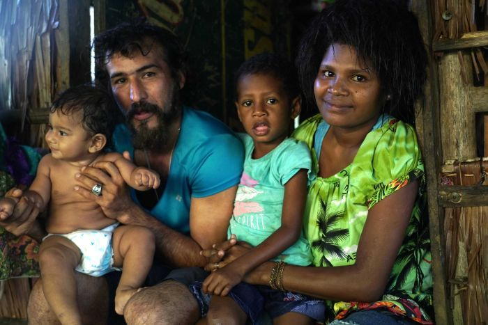 A father holds his baby while sitting next to his wife and stepchild
