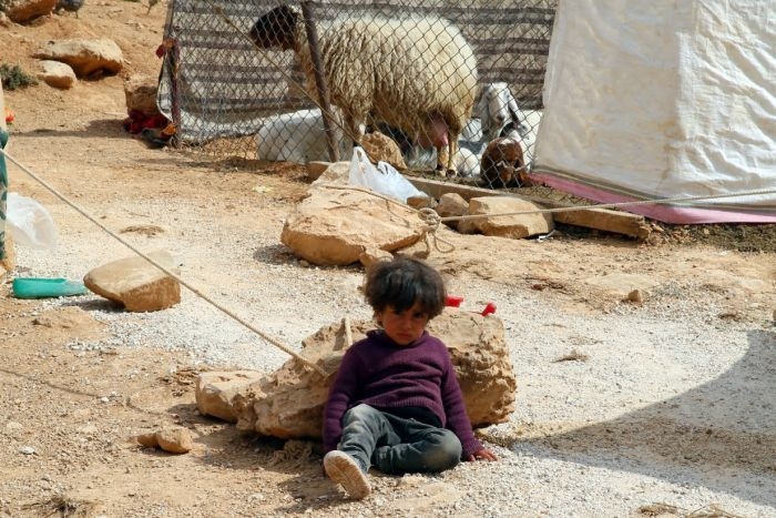 A boy sits in the dirt with a sheep behind and tents nearby.