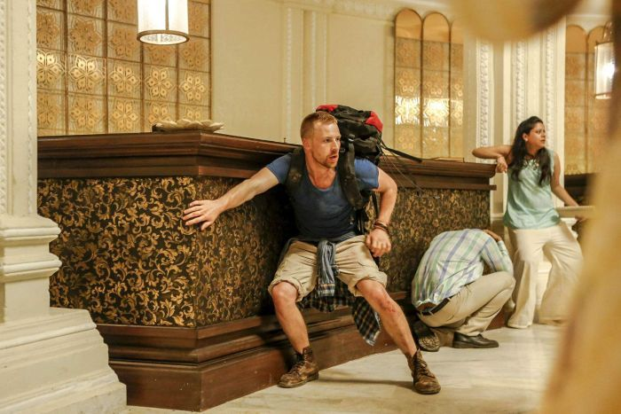 The actor crouches in fear in front of a hotel reception desk, seeking shelter from a threat out of frame.