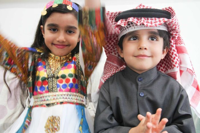 Two young children wearing the colourful traditional dress of Syria