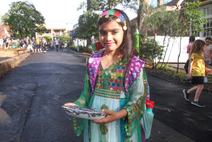 A girl, wearing colourful traditional clothes, carrying a plate of food outside a school