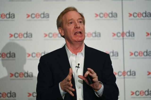 Brad Smith, wearing a black jacket and white shirt, makes a gesture with his hands as he stands speaking.