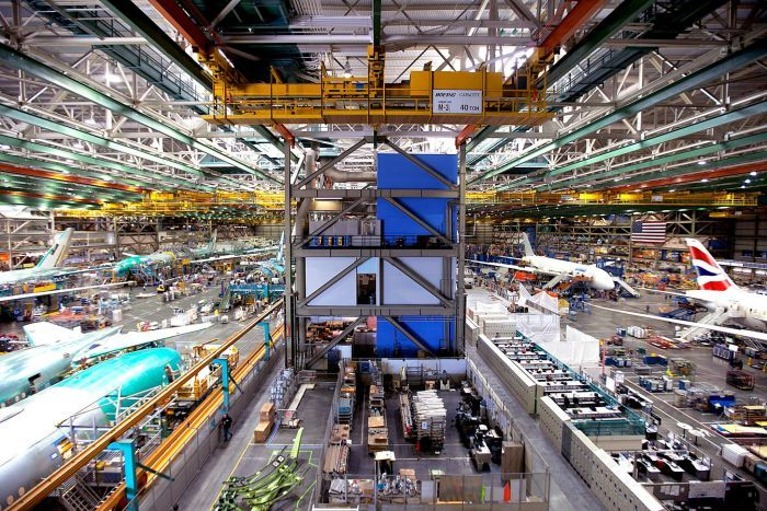 A vast wide-angle photo shows a large air hangar looking down on to a factory floor with multiple large Boeing jets.