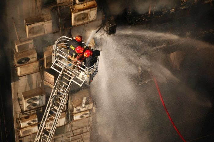 An aerial shot of firefighters in red helmets spraying water from a hose as they stand on a cherry picker.