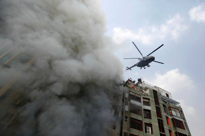 A chopper hovers to evacuate people stuck in a multi-storied office building that caught fire in Dhaka