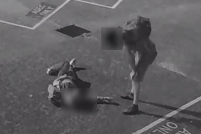 A man leans over another man, as pictures in grainy black and white CCTV image.