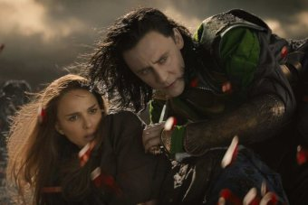 Loki protects Jane Foster as the red Aether explodes in front of them.